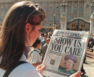 """Una mujer lee un periódico con el titular """"Show us you care"""" (Demuéstranos que te importa)"""