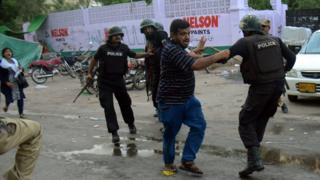 Pakistani policemen arrest an activist of the Muttahida Qaumi Movement (MQM) political party during a clash in Karachi on August 22, 2016.