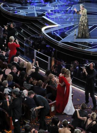 Frances McDormand stands on stage with her Oscar