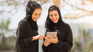 Two Abaya-wearing women looking at a tablet