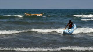 A man leads his traditional boat to shore, at the Saga on Lake Malawi, on July 17, 2011