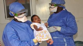 Medical workers present Noubia (C), the last known patient to contract Ebola in Guinea, during her release from a Doctors Without Borders treatment center in Conakry on November 28