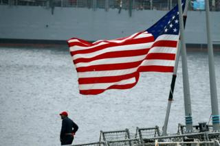 A member of the U.S. Navy Damage Control Training Team is seen near the U.S. national flag on the Arleigh Burke-class guided-missile destroyer USS Fitzgerald, which has been damaged from colliding with a Philippine-flagged merchant vessel, at the U.S. naval base in Yokosuka, south of Tokyo, Japan 18 June 2017