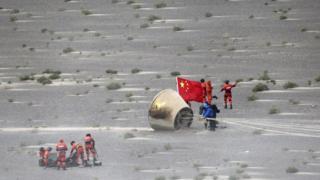 26 Haziran'da çekilen bu görüntülerde Çinli yetkililerin Çin bayrağı ile roketi incelediği görülüyor.