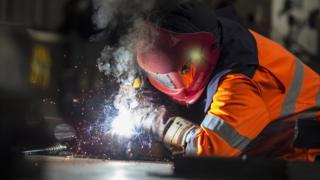 Steel worker cutting metal