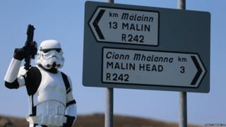 Star Wars fan John Joe McGettigan in stormtrooper costume beside a road sign near Malin Head