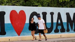 """Turistas caminan por delante de un cartel que dice, en inglés, """"yo amo Guam""""."""