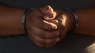 """руки в наручниках одного из задержанного в ходе рейдов против """"Мара Сальватруча"""""""