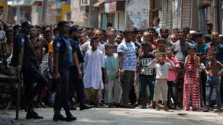 Bangladeshis gather near a shooting scene in Narayanganj, outskirts of Dhaka, Saturday, Aug. 27, 2016.