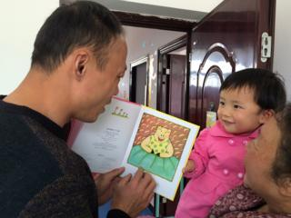Family planning officer Li Bo reads a story for two-year-old Liu Siqi