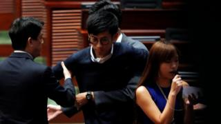 Security guards block pro-independence legislator-elects Baggio Leung and Yau Wai-ching (R) from retaking their oaths inside the Legislative Council in Hong Kong, China November 2, 2016.