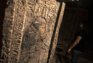 """A woman looks on at ancient Egyptian inscriptions inside Maya""""s tomb at Saqqara""""s ancient burial grounds in Giza, Egypt, 16 September 2017."""