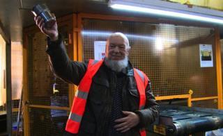 Festival organiser Michael Eavis holding a stainless steel cup