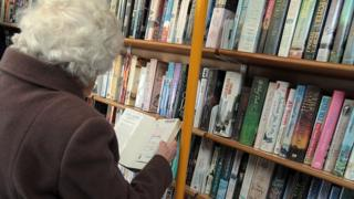 woman reading book at library