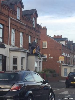 Youths on roof in Holylands, Belfast, 20 September 2016