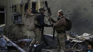 Iraqi forces carry weapons in the Mosul district of Wahda, 8 January 2017