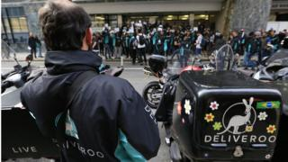Deliveroo riders holding a protest over pay outside the company HQ in London, as the food delivery company has been told by the Government that it must pay its workers the minimum wage unless it reaches agreement in the courts to treat them as self-employed.