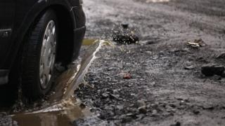 A car driving through a pothole