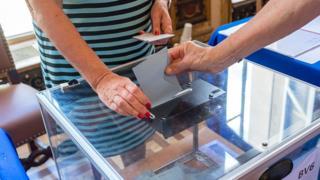Un français accomplit son devoir citoyen dans un bureau de vote à Paris