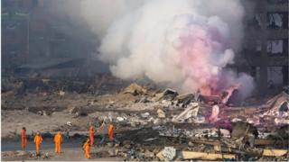 Firefighters in protective gear watch partially pink smoke continue to billow after an explosion at a warehouse in Tianjin (13 August 2015)