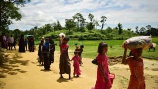 রোববার বালুখালি শিবিরের পাশ দিয়ে হেঁটে যাচ্ছেন রোহিঙ্গা শরণার্থীরা