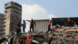 rescuer in high vis jacket pointing and shouting, while standing on debris next to a tall building