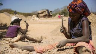 Woman and child breaking rocks from cobalt mine