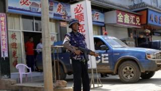 Lính chính phủ Myanmar đứng gác ở đường phố đầy chữ Hán của Laukkai, thủ phủ Kokang
