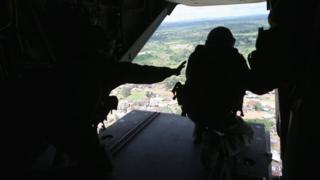 Silhouette of US Marine looking out of an MV-22 Osprey tiltrotor