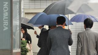 Pedestrians walk past signage of Nomura Securities in front of its branch in Tokyo