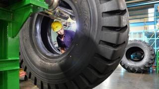 An Indian employee checks tyres for faults at the JK Tyre and Industries manufacturing plant in Mysore