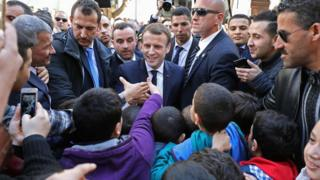 French President Emmanuel Macron is surrounded by security as he greets children in the streets of Algiers, Algeria- Wednesday 6 December 2017