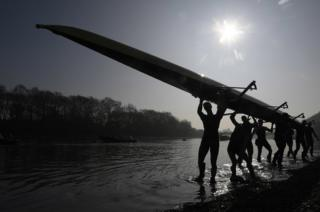 Oxford University men's boat crew carry their boat out of the water following training on the River Thames ahead of this year's Oxford v Cambridge Boat Race in London on Sunday