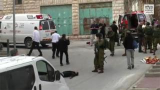 A scene from the video showing a soldier raising his gun at the wounded Palestinian