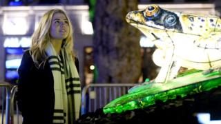 Woman looks at lit-up frog as part of Lumiere Festival