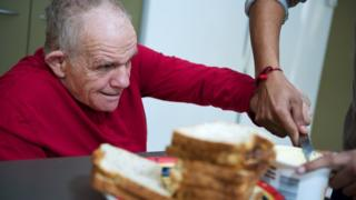 A man receiving help to spread butter on bread