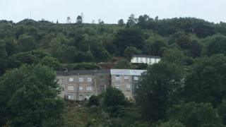 The row of houses stand on a hillside in the Swansea Valley
