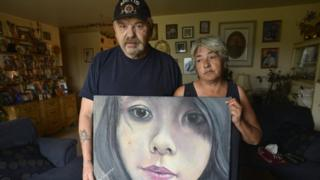 Joe and Thelma Favel display a framed painting of their niece, Tina Fontaine, who was murdered and her body dumped in the Red River