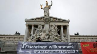 Austrian police officers stand behind a banner in front of the Parliament in Vienna