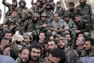 Syrian President Bashar al-Assad poses for photos with soldiers near the frontline in the Eastern Ghouta on 18 March 2018