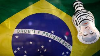 A Brazilian flag and a inflatable doll of former President Lula in prison clothes can be seen at a protest on 12 May 2016