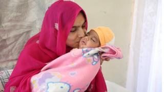 Tayyaba Anjum Ali kissing newborn son