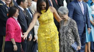 """First lady Michelle Obama directs Ho Ching, right, wife of Singapore""""s Prime Minister Lee Hsien Loong, where to stand during a state arrival ceremony on the South Lawn of the White House in Washington, Tuesday, Aug. 2, 2016"""