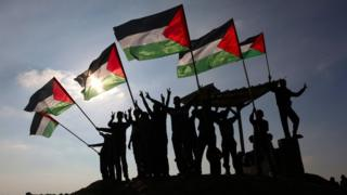 Palestinian protesters wave Palestinian flags near the Israel-Gaza border fence on 9 January 2018
