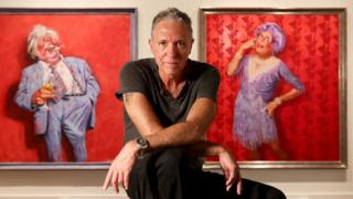 Bill Leak poses in front of two painting of Australian comedian Barry Humphries
