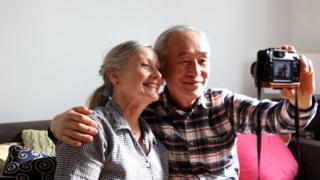 Пожилые мужчина и женщина фотографируют себя