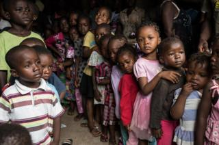 Children staying in the half built house queue up to receive clothes donated by some Lebanese women who live in Freetown