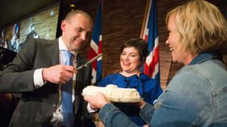 Gudni Johannesson (L) cuts a cake next to his wife Eliza Reid