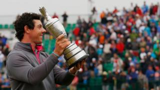 rory mcilroy holds aloft the trophy in front of spectators