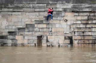 A couple exchanges kisses on the bank as high waters causes flooding along the Seine River in Paris, France